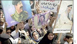 Crowd in Baghdad carry banners depicting Saddam Hussein
