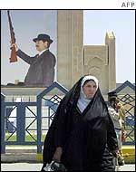 A woman walks by a Saddam Hussein poster in Baghdad
