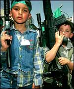 Palestinian children carrying toy guns