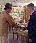 Colonel Muammar Gaddafi (l) greets UK Foreign Office Minister Mike O'Brien