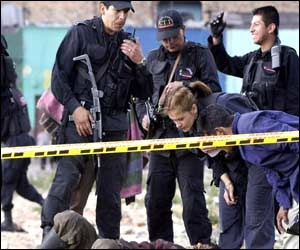 Police examine the body of a victim from one of the explosions in Bogota