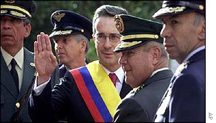 Colombian President Alvaro Uribe, with armed forces chiefs, waves to supporters