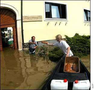 A firefighter (R) delivers bread and water to people who remain in their flooded houses in Lower Austria