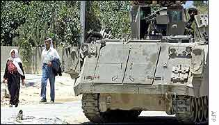 Palestinians pass by an Israeli tank
