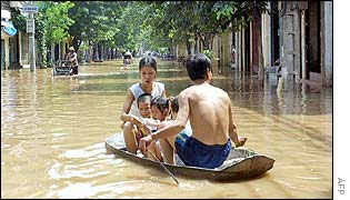 Family in flooded street in north Vietnam