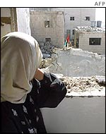 Palestinian woman looks at demolished home of a suicide bomber