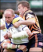 Mark Hilton's charge is halted by Castleford's Wayne Bartim (right)