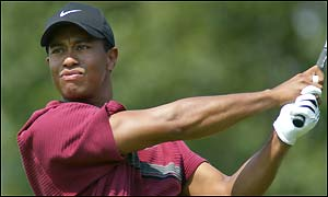 Tiger Woods punches an iron shot down the fairway