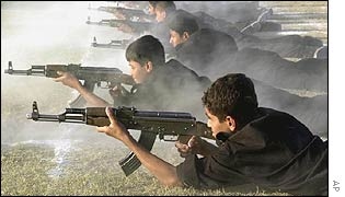 Iraqi schoolboys practise firing assault rifles at a summer military camp.