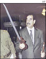Saddam Hussein inspects a sword he received for his 65th birthday on 10 August 2002.