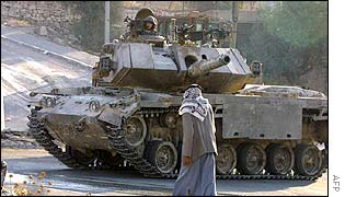 A Palestinian man walks past an Israeli tank