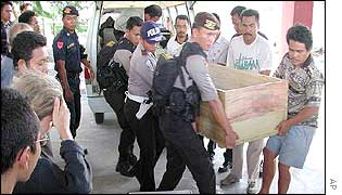 Officials carry the body of Lorenzo Tadey, an Italian tourist killed on 9 August 2002