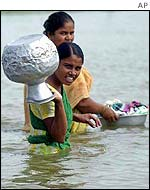Bangladeshi women wade through flood water