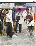People avoid waves created by passing vehicles as they walk through the flooded streets of Manila
