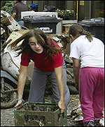 Two girls try to clear muddy flood debris