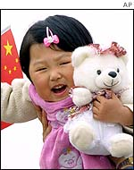 A girl cuddles a toy bear while waving the national flag