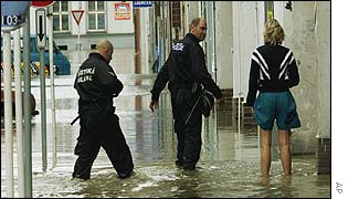 Police question a woman in a flooded suburb of Prague