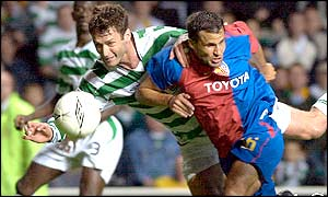 Chris Sutton wins an aerial challenge with Basel's Gregory Duruzduring at Celtic Park