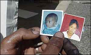 Ambassanger Hailu holding photos of his wife and son
