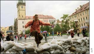 A tourist jumps over sandbags in the Old Town