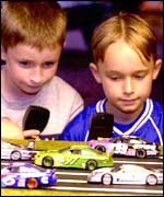 Boys playing with Scalextric cars