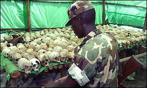 Soldier looks at bones of the genocide victims