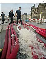 Firefighters walk alongside hoses pumping water out of Zwinger and the Semper opera house, background, in the eastern German city of Dresden