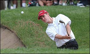 Justin Rose plays out of a bunker on the first hole at Hazeltine