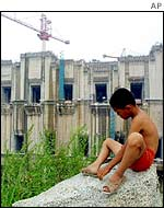 A boy sits near the construction of the Three Gorges dam