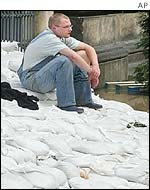 Dresden resident sitting on sandbags