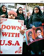 Iranian young women hold signs at a demonstration