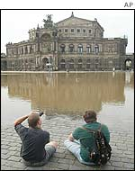 People sit in front of the Semper Opera House in Dresden