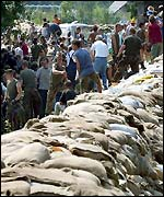Hundreds of volunteers build embankments with sandbags