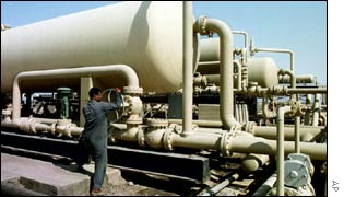 An Iraqi oil worker checks pipes at the West Qurna oil field in Iraq