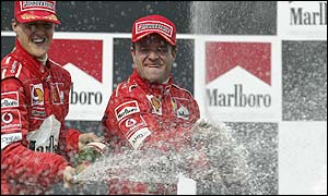 Rubens Barrichello and Michael Schumacher celebrate Ferrari's constructors title