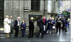 Argentine people queue outside a bank