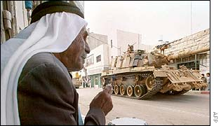 Palestinian man watches tank roll past near Ramallah