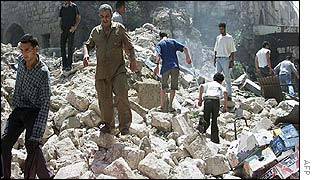Palestinian men make their way through a pile of rubble after Israeli troops blew up a row of shops in Nablus