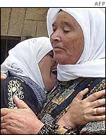The mother of 13-year-old Mahmud Abu Oudeh cries on his grandmothers shoulder