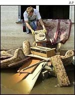 Woman removes debris from flooded house