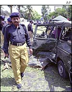 Police examine a damaged vehicle outside the US Consulate in Karachi