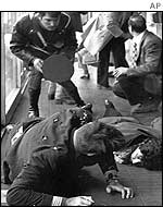 Two unidentified people lie injured on the floor of Rome's Fiumicino airport where guerrillas hijacked a plane in 1973