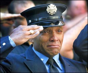 A firefighter can't hold back the tears during a ceremony to mark Sept 11