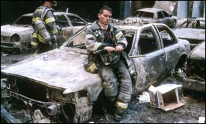 Jeff Straub leans onto the debris of a wrecked car at ground zero