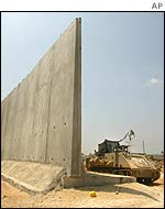 An Israeli armoured personnel carrier guards a gap in the newly built wall separating the West Bank town of Qalqiliya from Kfar Saba in Israel