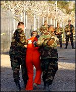 Detained prisoner is held by US soldiers at Guantanamo Bay, Cuba