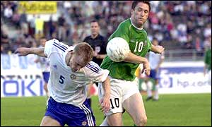 Goalscorer Robbie Keane forces his way past Hannu Tihinen