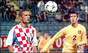 Tomislav Maric (left) and Wales' Mark Delaney run for possession of the ball during the 1-1 draw in Croatia