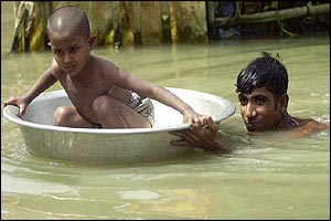 Man takes his son away from floodwaters in a household utensil, near Dhaka