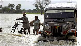 Indian villagers cross the flooded river Gandak